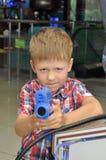 Menino com as armas nas máquinas de jogo do salão Imagens de Stock Royalty Free