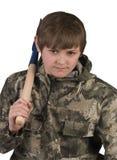 Menino com as ferramentas de jardinagem no ombro em um terno protetor Foto de Stock Royalty Free