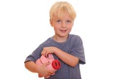 Menino com banco piggy Imagem de Stock Royalty Free