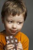 menino com barra de chocolate imagens de stock royalty free