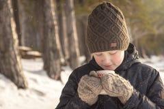 Menino com a bebida quente do inverno exterior fotos de stock royalty free
