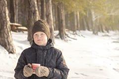 Menino com a bebida quente do inverno exterior imagens de stock