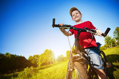 Menino com a bicicleta que está de encontro ao céu azul Imagem de Stock Royalty Free
