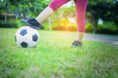 Menino com a bola na grama verde com fundo da luz do sol Imagem de Stock
