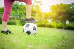 Menino com a bola na grama verde com fundo do por do sol Fotos de Stock
