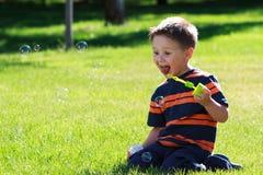 Menino com bolhas de sabão fotografia de stock