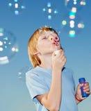 Menino com bolhas de sabão de encontro a um céu Imagens de Stock