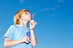 Menino com bolhas de sabão de encontro a um céu Imagens de Stock Royalty Free