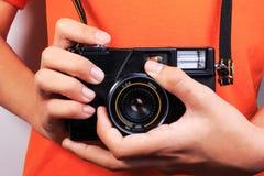 Menino com a câmera no fundo alaranjado da camisa foto de stock