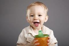 Menino com copo do suco Fotos de Stock