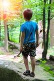 Menino com curva e setas em uma caminhada no parque imagem de stock