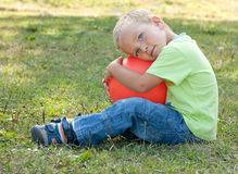 Menino com a esfera que senta-se na grama verde. Imagens de Stock Royalty Free