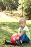 Menino com a esfera que senta-se na grama verde. Imagens de Stock
