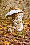Menino com a estátua do guarda-chuva coberta pelas folhas fotografia de stock