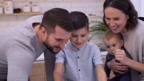 Menino com a família que joga o jogo na tabuleta digital vídeos de arquivo