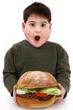 Menino com fome obeso com hamburguer gigante Fotos de Stock Royalty Free