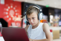 Menino com fones de ouvido usando um portátil Fotografia de Stock