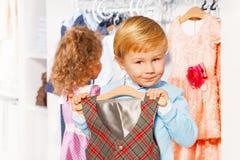Menino com gancho e veste, menina que escolhe a roupa Imagens de Stock