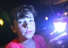 Menino com a lanterna elétrica na noite foto de stock royalty free