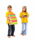 Menino com livros pesados, e uma menina que tenha um eBook Foto de Stock Royalty Free