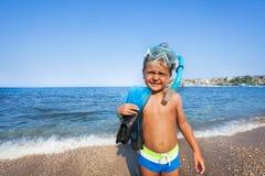 Menino com máscara do mergulhador e pás no litoral imagem de stock