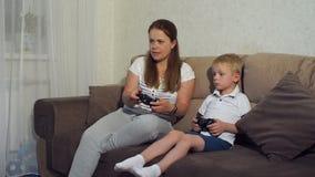 Menino com a mãe que senta-se no sofá e que joga no jogo de ação na televisão video estoque
