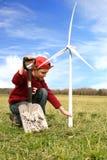 Menino com moinhos de vento e pá no campo Fotografia de Stock