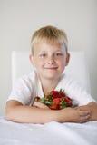 Menino com morangos Foto de Stock Royalty Free