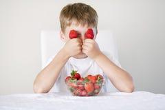Menino com morangos Fotografia de Stock