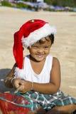 Menino com o chapéu do Natal na praia Fotografia de Stock