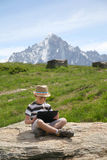O menino com PC da tabuleta senta-se na pedra Imagem de Stock Royalty Free