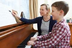 Menino com o piano de Having Lesson At do professor de música foto de stock