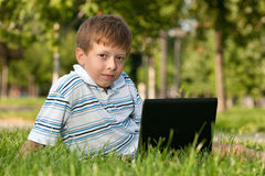 Menino com o portátil no gramado Foto de Stock Royalty Free