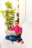 Menino com o portátil no sofá Imagem de Stock Royalty Free
