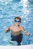 Menino com os óculos de proteção na piscina imagem de stock royalty free