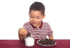 Menino com os bolinhos e o leite do sanduíche do chocolate Fotografia de Stock