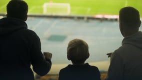 Menino com os irmãos que olham emocionalmente o futebol no estádio, excitado com jogo filme