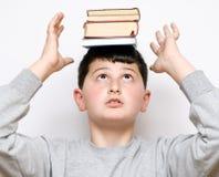 Menino com os livros em sua cabeça Imagens de Stock Royalty Free