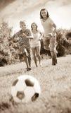 Menino com os pais felizes que jogam no futebol Imagens de Stock Royalty Free