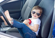 Menino com os vidros e a maçã vermelha que sentam-se no carro Fotos de Stock