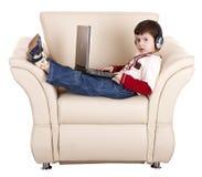 Menino com portátil e auscultadores. imagem de stock royalty free