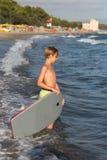 Menino com pouca prancha na linha costeira com ondas: Conceito das férias de verão Fotos de Stock Royalty Free