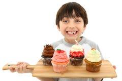 Menino com queques e crosta de gelo Imagens de Stock