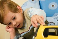 Menino com seu carro do brinquedo Imagens de Stock Royalty Free