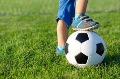 Menino com seu pé em uma esfera de futebol Imagens de Stock Royalty Free