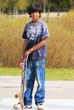Menino com skate Foto de Stock Royalty Free
