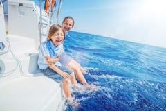 Menino com sua irmã a bordo do iate da navigação no cruzeiro do verão fotos de stock