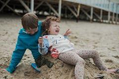 Menino com sua irmã que joga na praia Foto de Stock
