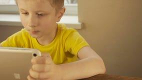 Menino com tablet pc, vista próxima Tiro da zorra video estoque