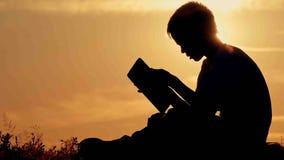 Menino com a tabuleta no por do sol que senta-se na montanha Imagem de Stock Royalty Free